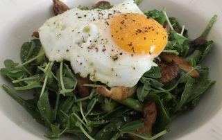 Sunny side up egg over spinach salad dressed with Gremolata olive oil and lemon bouquet balsamic