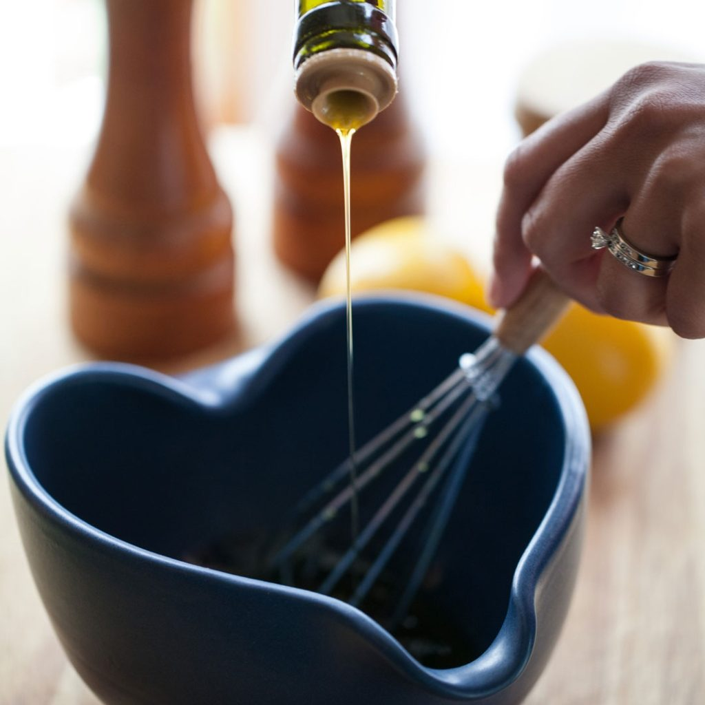 olive oil drizzled into bowl with hand whisking