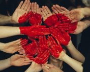multiple hands dipped in red forming a heart