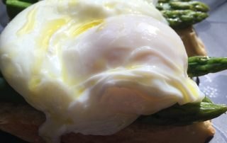 poached eggs on asparagus and crostini finished with olive oil