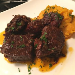 braised beef plated on whipped sweet potato