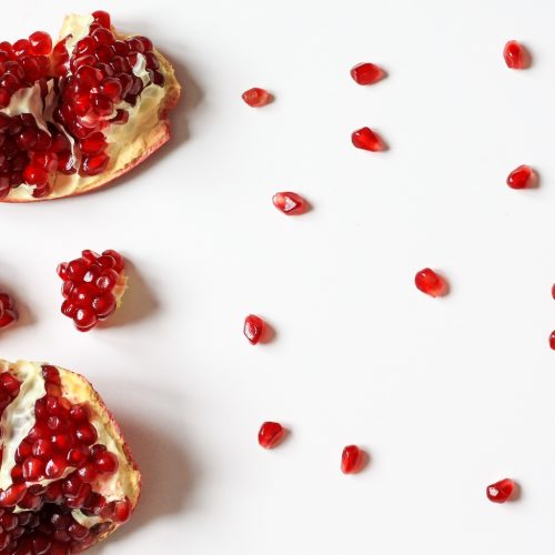 overhead shot of pomegranate seeds on white background