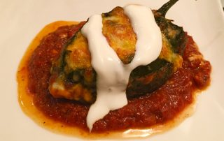 stuffed poblano peppers with melted cheese topped with key lime sour cream